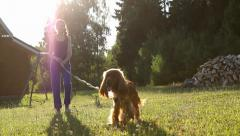 Girl and dog walking in the garden on summer day, sun rays Stock Footage