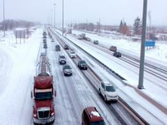 A traffic jam of cars and trucks down a cleared snow highway in a snow storm. Stock Footage