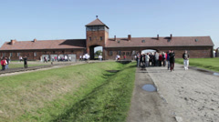 Visitors at Auschwitz Birkenau - main gate and railway line Stock Footage