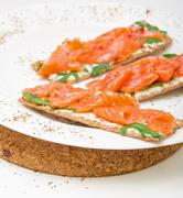 Salted salmon on crispy bread with cheese and arugula Stock Photos