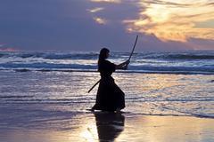 young samurai women with japanese sword(katana) at sunset on the beach - stock photo