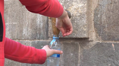 Hands filling bottle water from street fountain Stock Footage