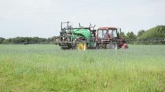 Tractor fertilizing wheat field in summer day Stock Footage