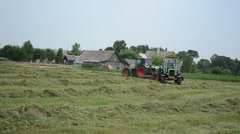Heavy agricultural machines prepare hay animal fodder in field Stock Footage