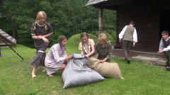 Girls with nice dresses cram hay in large linen bags Stock Footage
