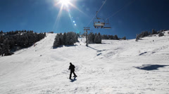 Ski Lift Moves Over The Snowy Mountain And The Sun Ray. Stock Footage