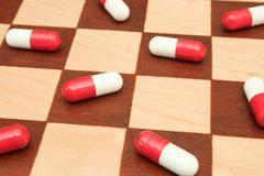 Pills on chessboard Stock Photos