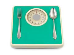 Fork and spoon on weight scale Stock Photos
