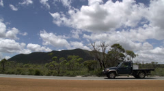 Pan from the road with cars passing by  through the Stirling Ranges Stock Footage