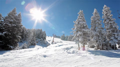 Sunny day in the snowy mountain and ski lift moves up with skiers. Stock Footage