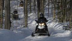 Three Snowmobiles Ride Through the Forest Stock Footage