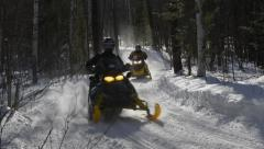Four Snowmobiles Zoom Down the Trail Stock Footage