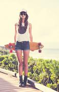 Hipster girl with skate board wearing sunglasses Stock Photos