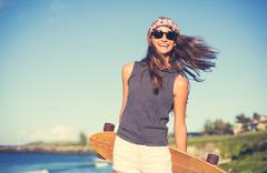 hipster girl with skate board wearing sunglasses - stock photo