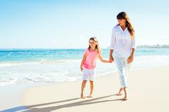 happy mother and young daughter walking on the beach - stock photo