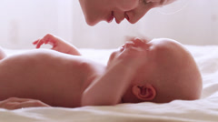 Mom stroking and kissing newborn baby Stock Footage