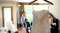 SDOF of wedding dress hanging with bride in background Stock Footage