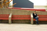 Stock Photo of Woman on red bench