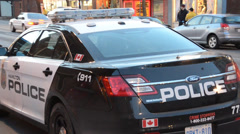 Black and White Police Car on Busy Street Stock Footage