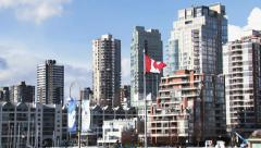 Canadian Flag waving with High Rise Building in the Background - stock footage