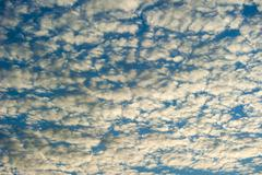 sky with fluffy clouds lit bij the sun - stock photo