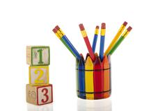 collage of colourfull pencils in a cup next to three 1-2-3 cubes - stock photo