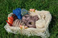 Stock Photo of knitting yarn in basket on green grass