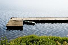 boat moored to old cracked wood bridge - stock photo