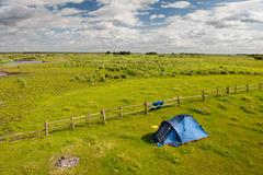 Camping tent and grass expanse landscape Stock Photos