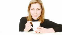 Smiling girl with golden hair drinking from a white cup Stock Footage