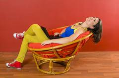 Woman relaxing at home in an armchair with a laptop Stock Photos