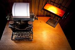 Desk with old typewriter and lamp - stock photo