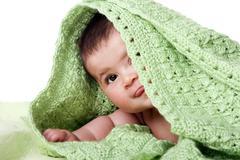 Cute happy baby between green blankets Stock Photos