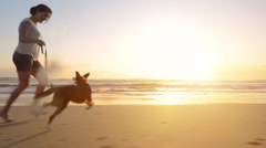 Woman running dog on beach lifestyle steadicam shot Stock Footage