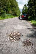 Potholes and rubbles in damaged woods road Stock Photos
