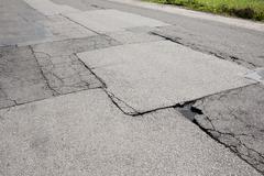 poor fixed chuckholes in asphalt damaged road - stock photo