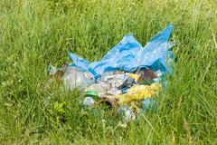 Illegal scatter garbage in blue plastic bag dump - stock photo