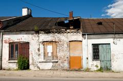 Derelict damaged cottage house with hole in roof - stock photo