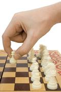 Pawn in hand and chessboard Stock Photos