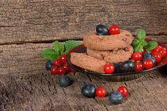 Chocolate cookies with blueberries and red currants Stock Photos