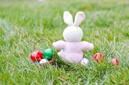 Stock Photo of Colorful easter eggs and rabbit on green grass