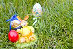 Easter eggs and rabbit hiding in the grass - stock photo