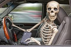 skeleton texting and driving - stock photo