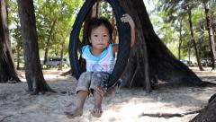 Thai child on a tire swing Stock Footage