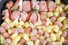 Saucepan with kebab, potatoes and wurstel Stock Photos
