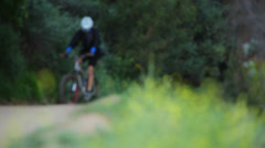 Man pedals mountain bike up hill Stock Footage