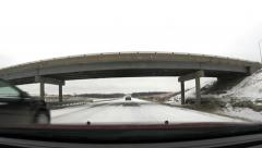 Going under overpass on snow packed road - stock footage