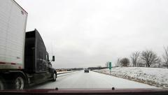 Unmarked 18 wheeler passing on a snow packed road - stock footage