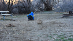 LITTLE BOY AND GIRL PLAYING IN THE DIRT IN THE COLD MORNING - stock footage