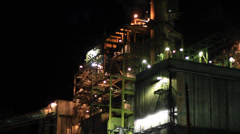 PAN OF A FACTORY AT NIGHT WITH LIGHTS LIT Stock Footage